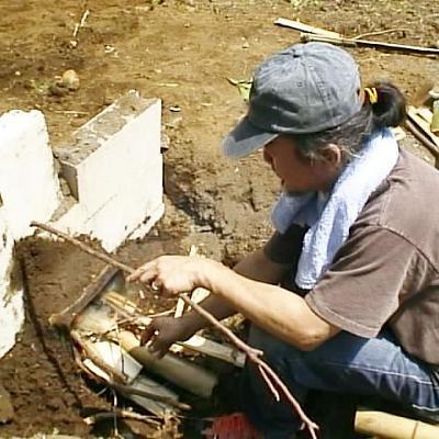 竹炭作りで窯に火をくべる
